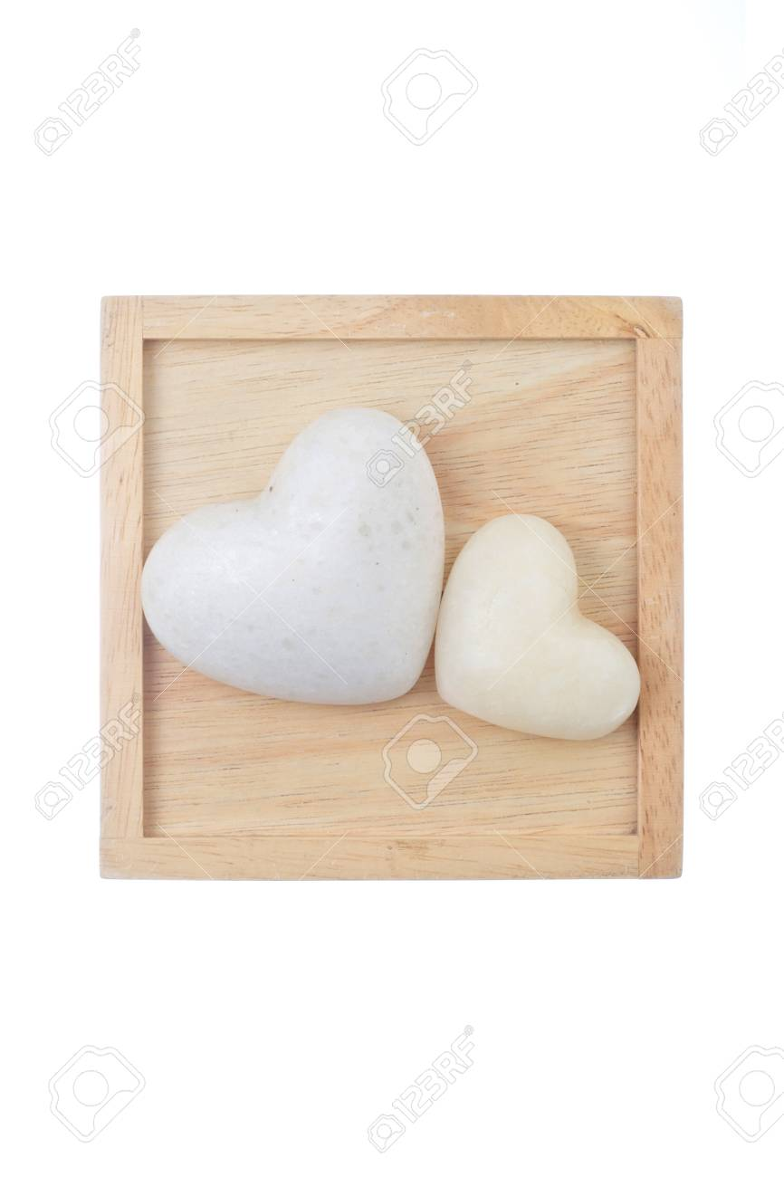 two white heart shaped stones on wood background Stock Photo - 14799519
