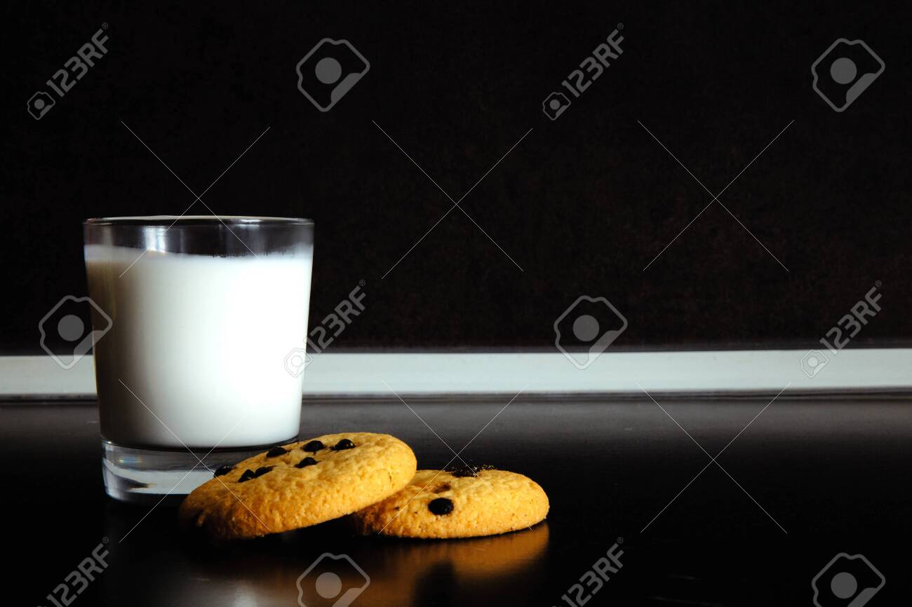 Good morning. Breakfast Cookies and a glass of milk. yogurt. Black background. black and white - 121183827