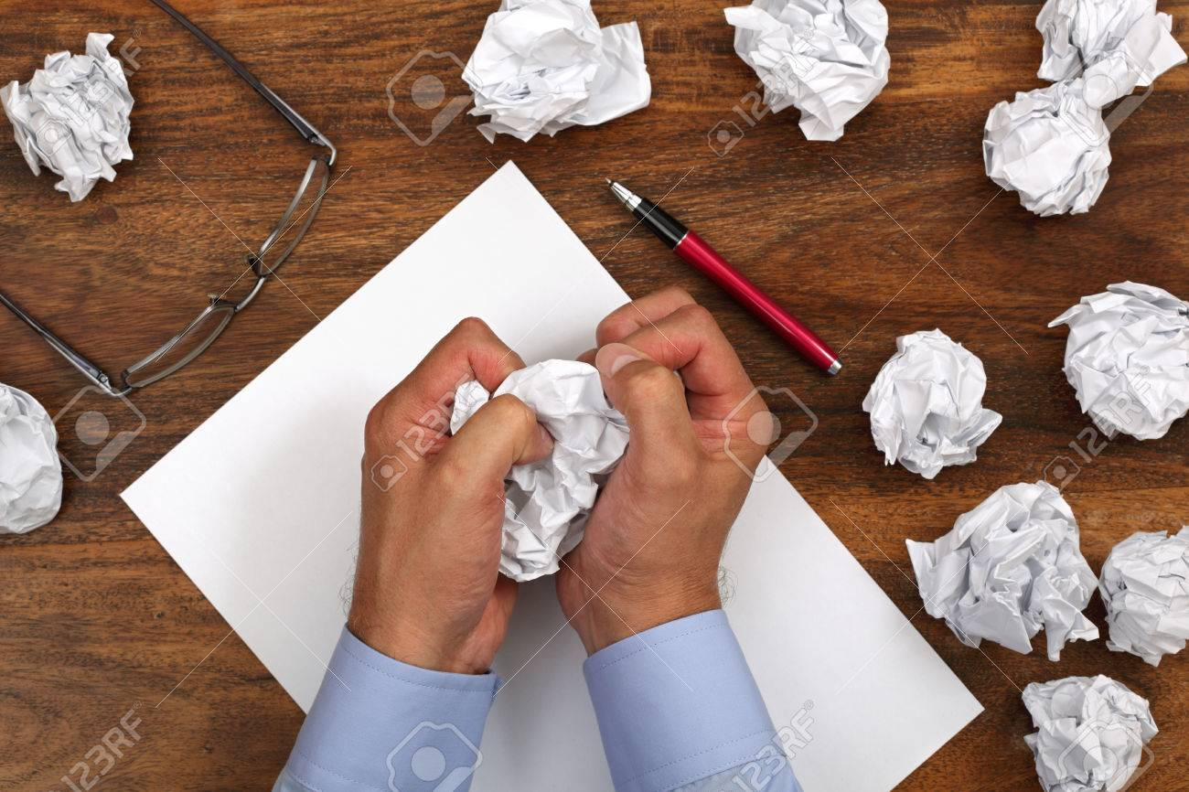 crumpled paper and businessman tearing up another paper ball.. stock