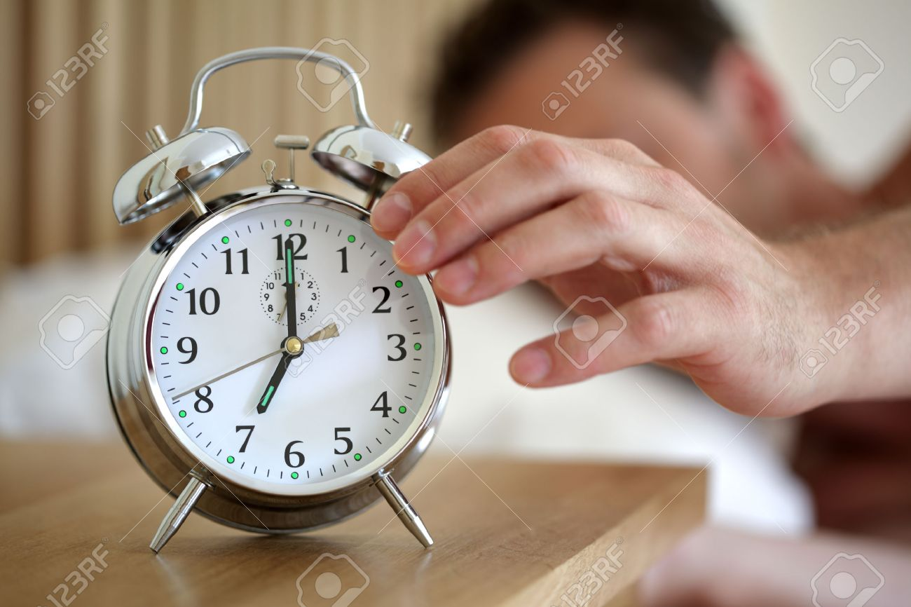 man lying in bed turning off an alarm clock in the morning at