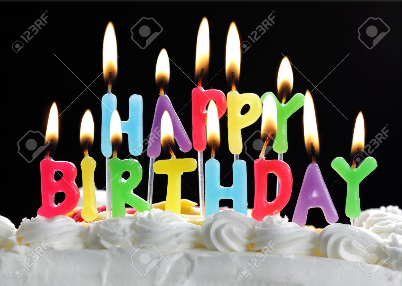 Colorful Happy Birthday Candles Burning On A Cake Stock Photo
