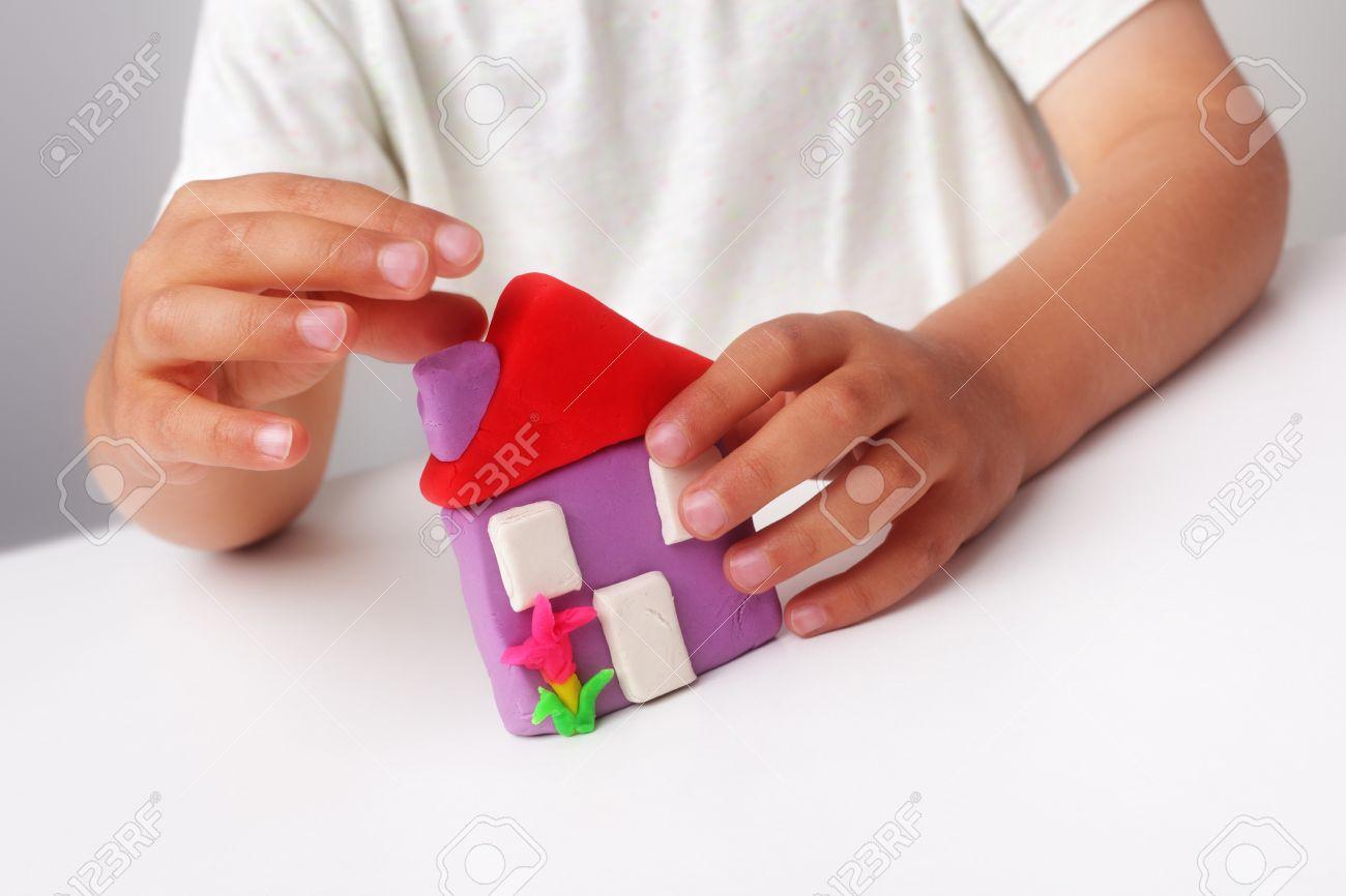 child building a plasticine house concept for construction child building a plasticine house concept for construction real estate family home and future