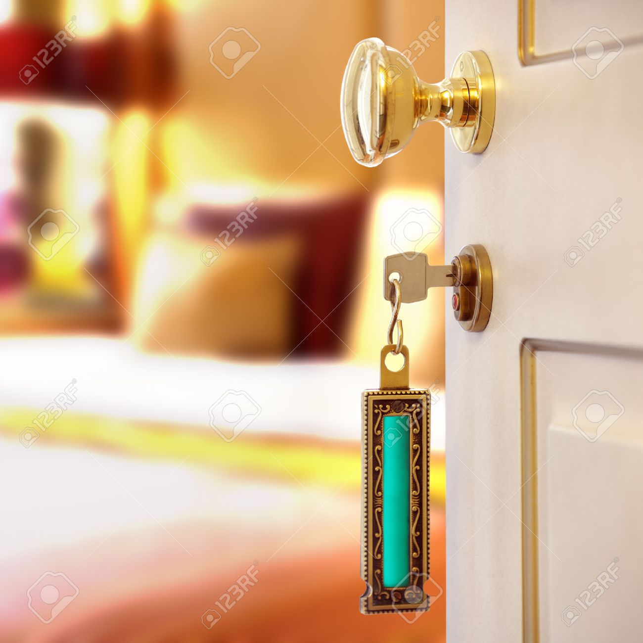 Hotel room or apartment doorway with key and keyring key fob in open door  and bedroom. Bedroom Key