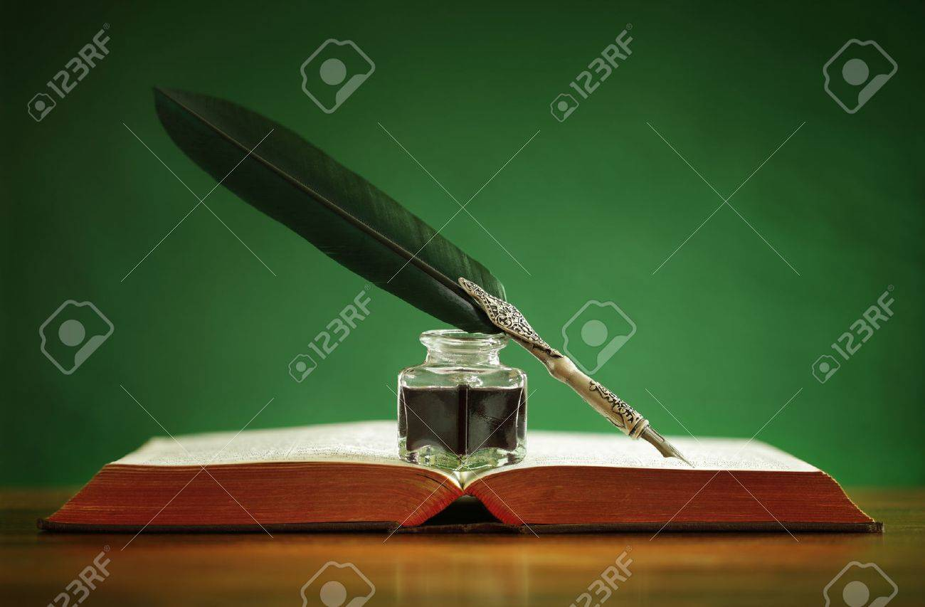 Quill pen and inkwell resting on an old book with green background concept for literature, writing, author and history Stock Photo - 29819611