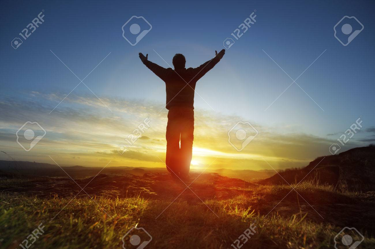 Silhouette of a man with hands raised in the sunset concept for religion, worship, prayer and praise - 35905364