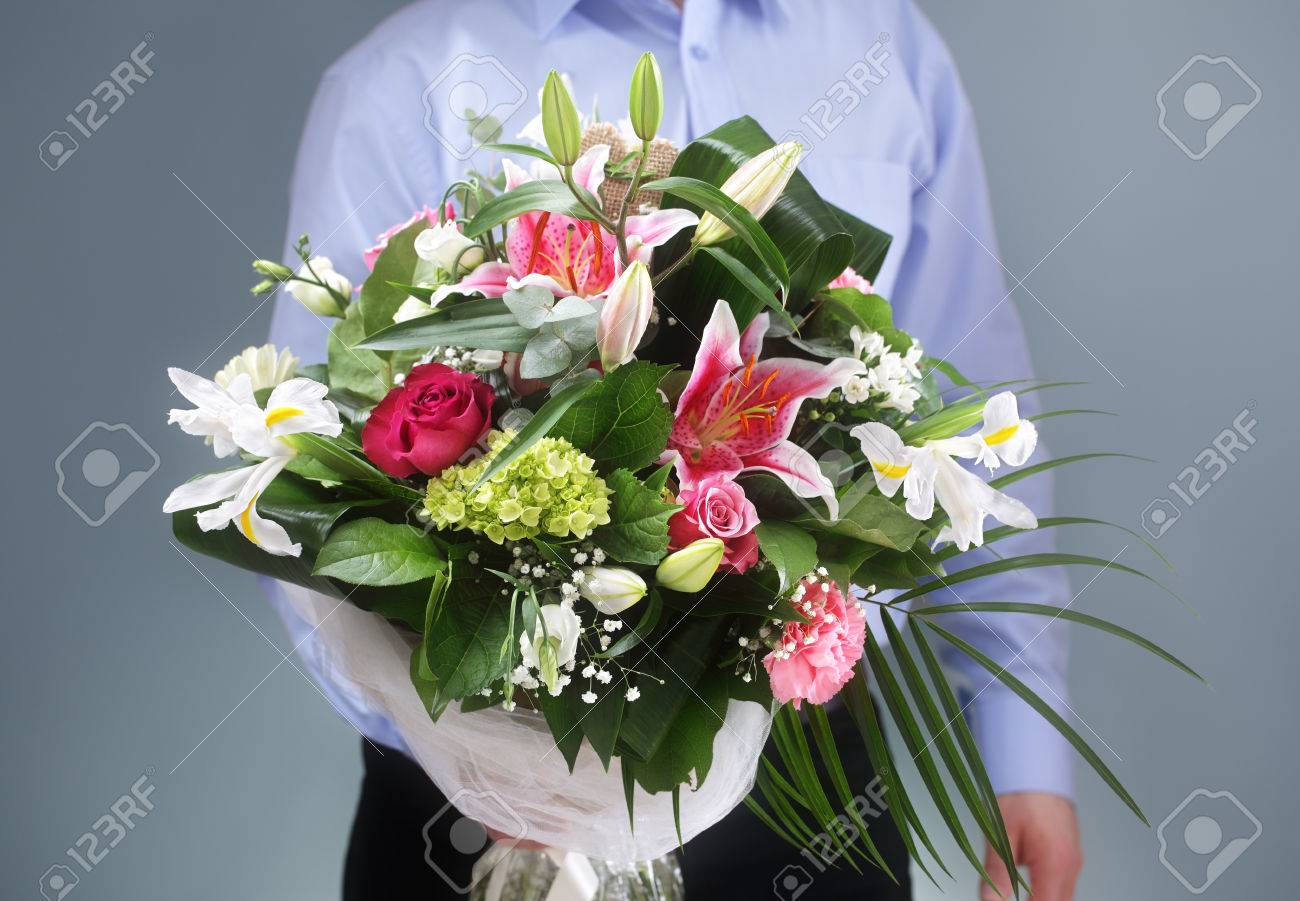 businessman holding and giving a bouquet of flowers stock photo