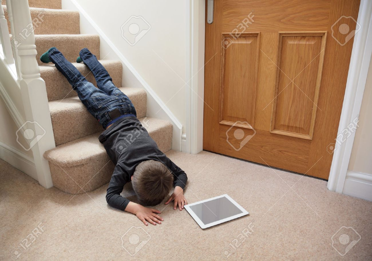Child Falling Down The Stairs Whilst Playing On Digital Tablet Not Concentrating Concept For Safety At