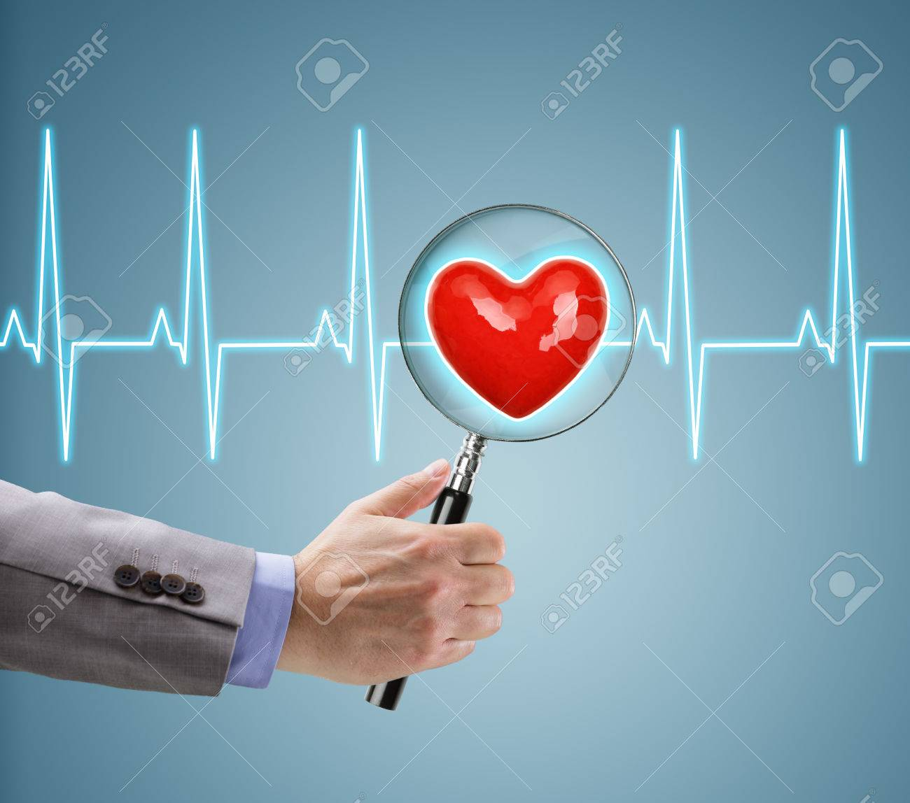 Heart health checkup, doctor with magnifying glass on a heart and ecg diagram - 48355386