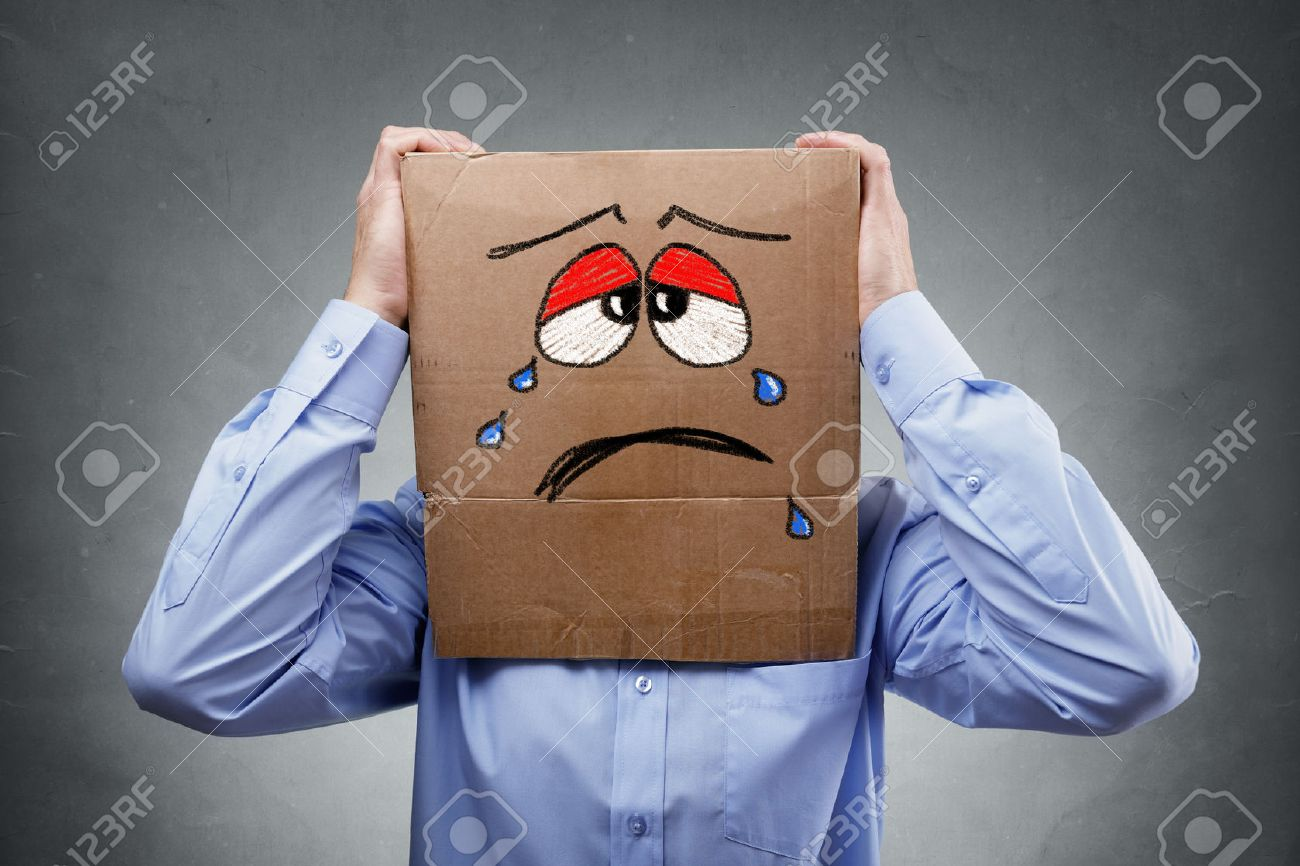 Businessman with cardboard box on his head showing a crying sad expression concept for headache, depression, sadness, heartache or frustration Standard-Bild - 48356011