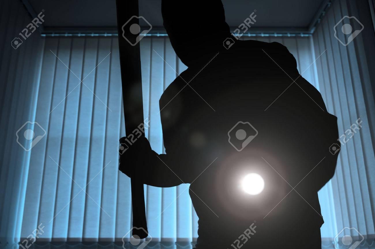Burglar or intruder inside of a house or office with flashlight and baseball bat Standard-Bild - 48356024