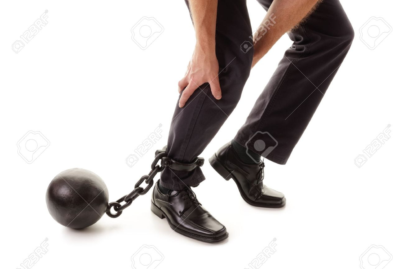 Ball and chain restraining a businessman as he tries to walk concept for business burden, willpower and determination Standard-Bild - 54427783