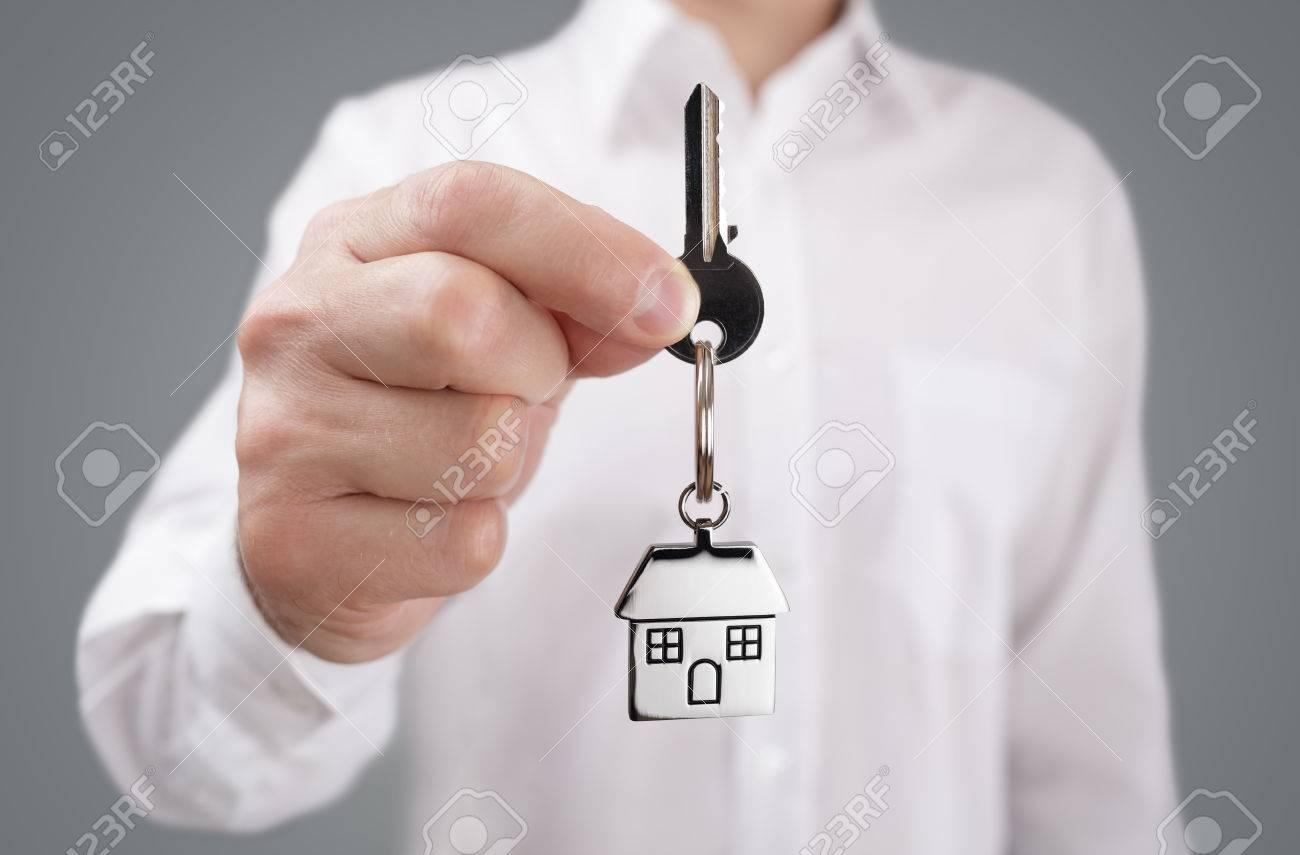 Man holding out house key on a house shaped keychain Standard-Bild - 54427791