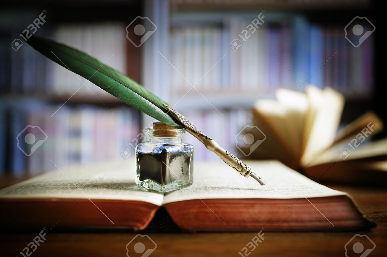 Quill pen and ink well resting on an old book in a library concept for literature, writing, author and history Standard-Bild - 54427796