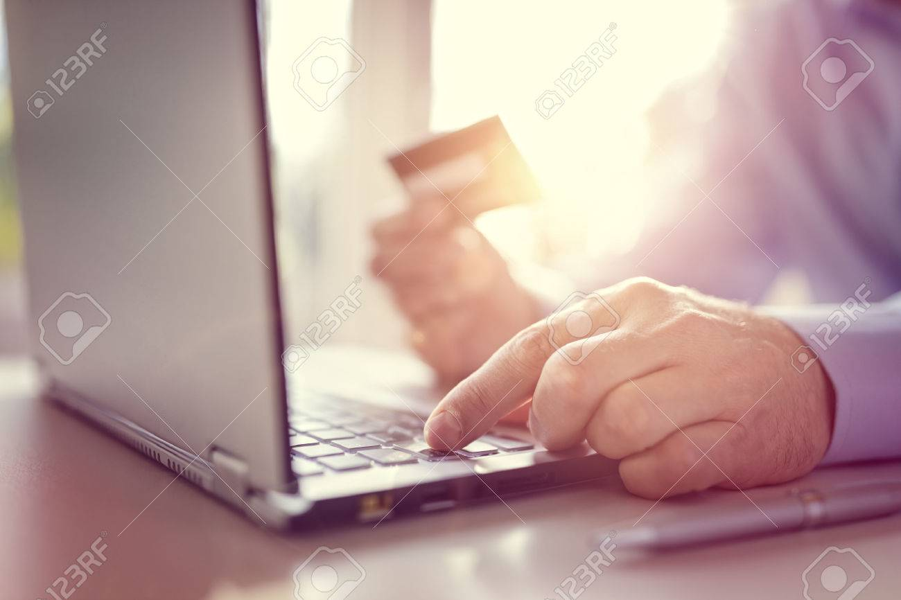 Man with credit card using a laptop computer for internet shopping Standard-Bild - 54427880