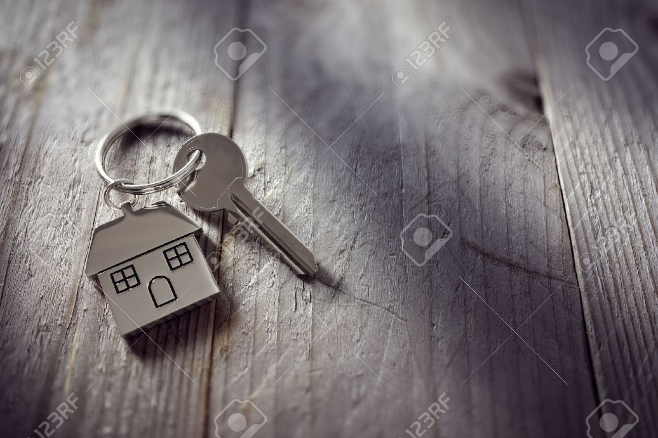 House key on a house shaped keychain resting on wooden floorboards concept for real estate, moving home or renting property - 54427924