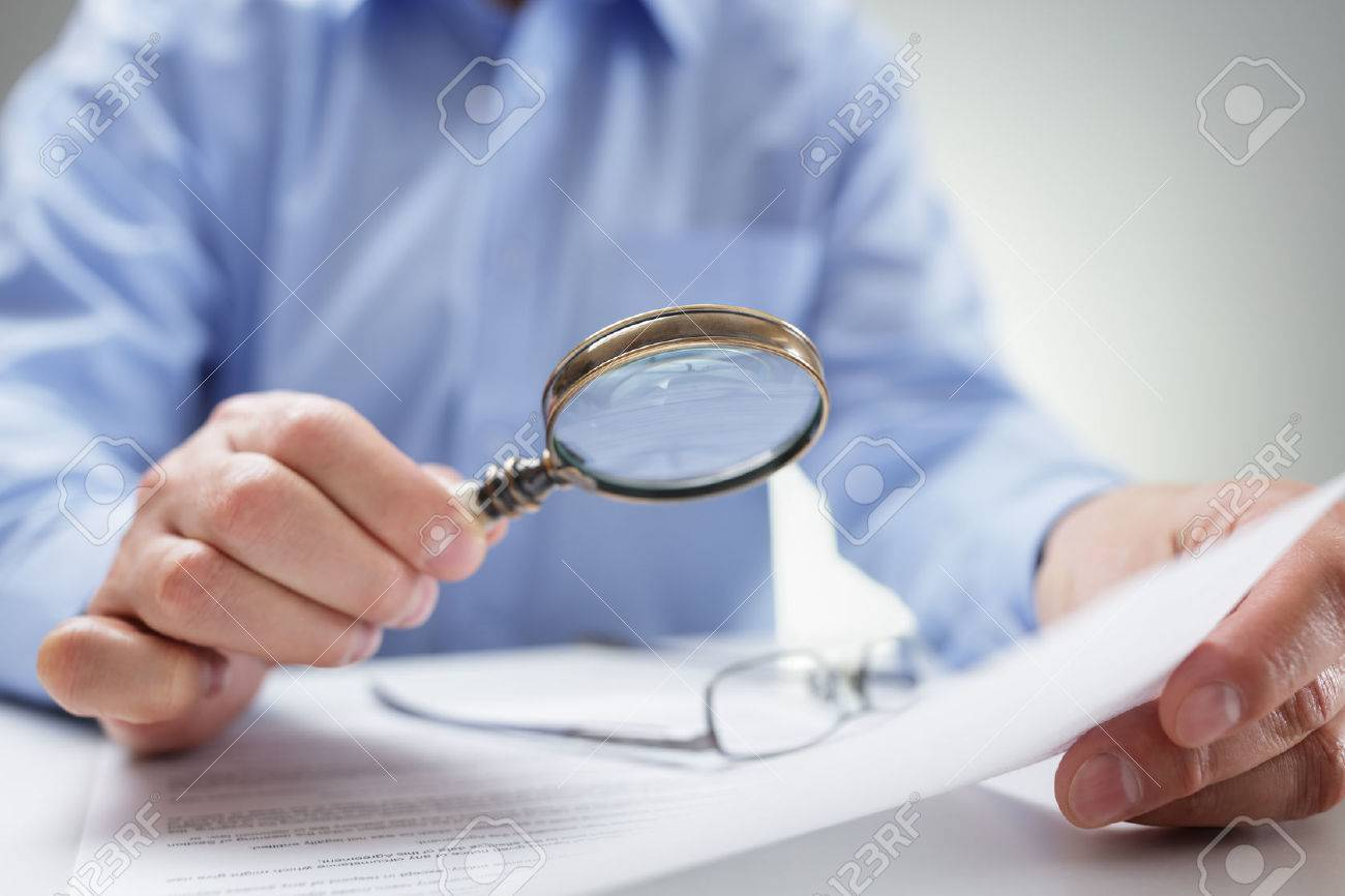 Businessman reading documents with magnifying glass concept for analyzing a finance agreement or legal contract Standard-Bild - 54428167