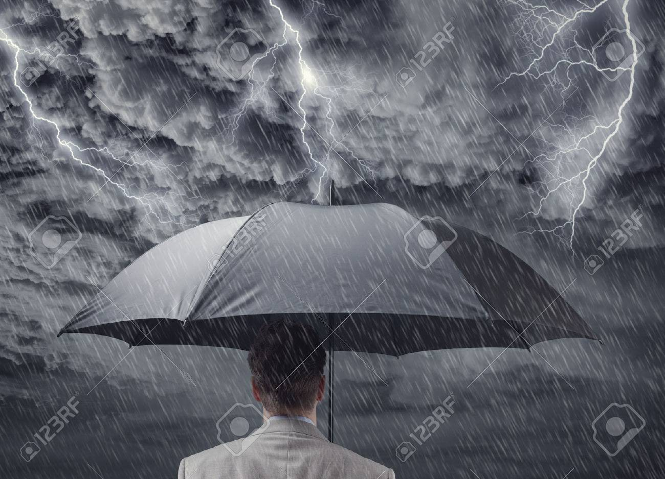 Businessman with black business umbrella protecting himself from the storm concept for insurance, financial protection from recession or economic depression - 54428257