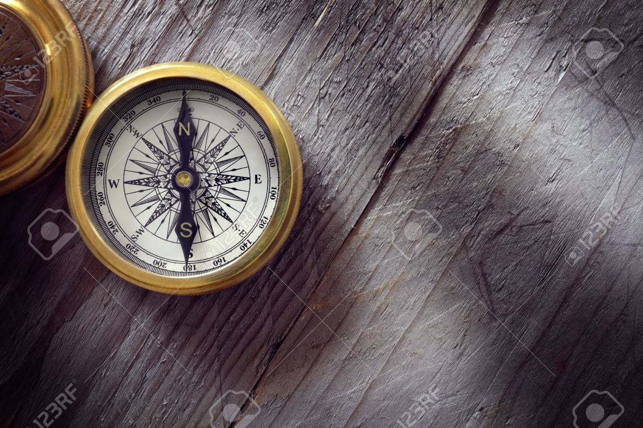 Antique golden compass on wood background concept for direction, travel, guidance or assistance - 54428265