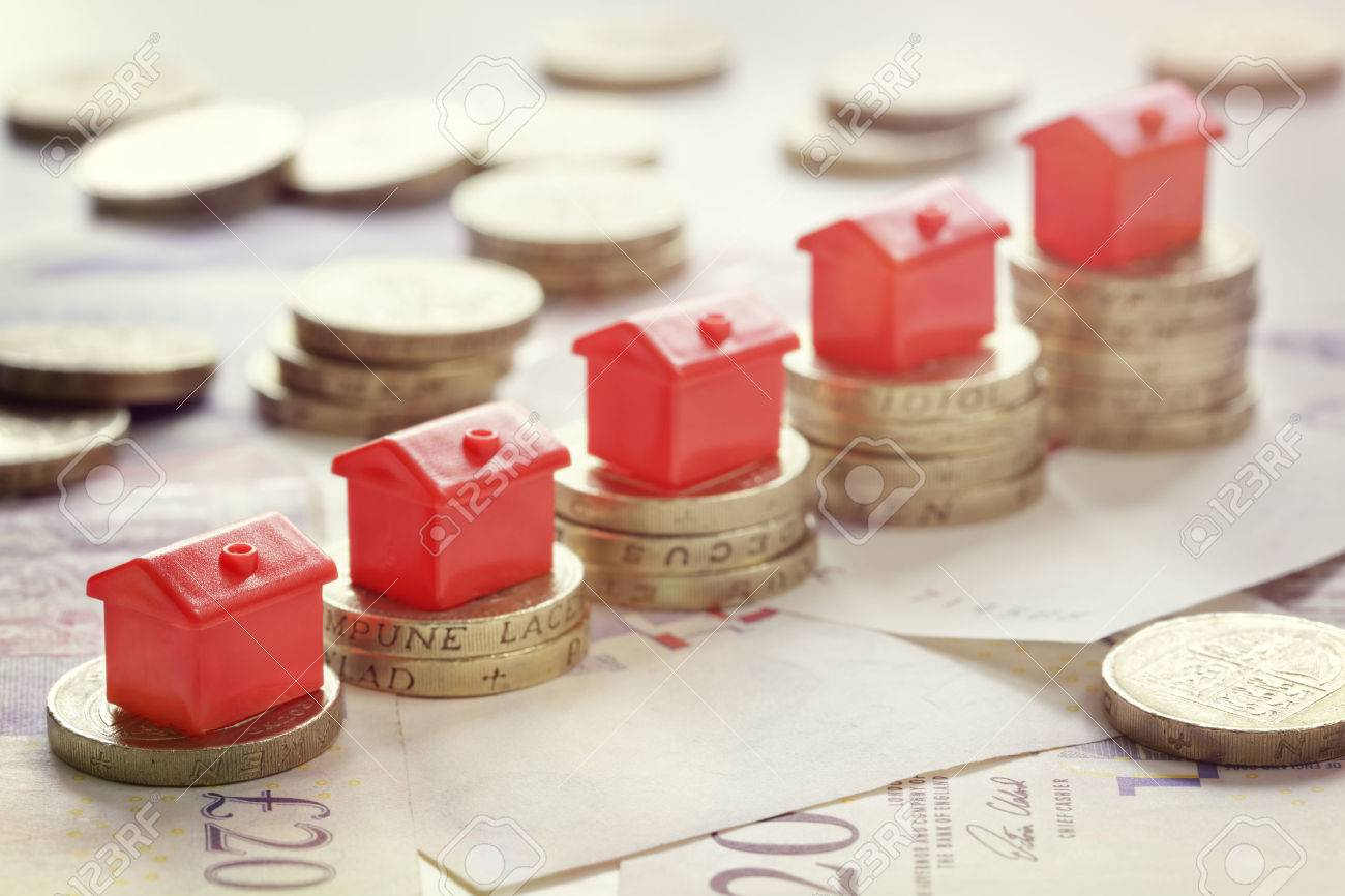 Minature houses resting on pound coin stacks concept for property ladder, mortgage and real estate investment Standard-Bild - 61386072