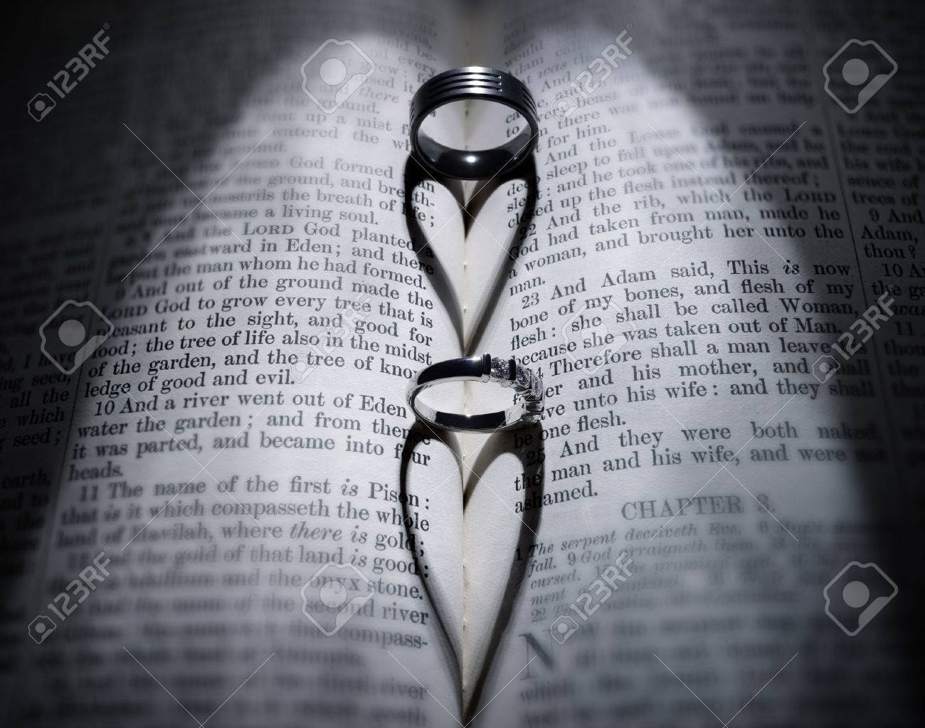 wedding rings casting heart shaped shadow over bible stock photo