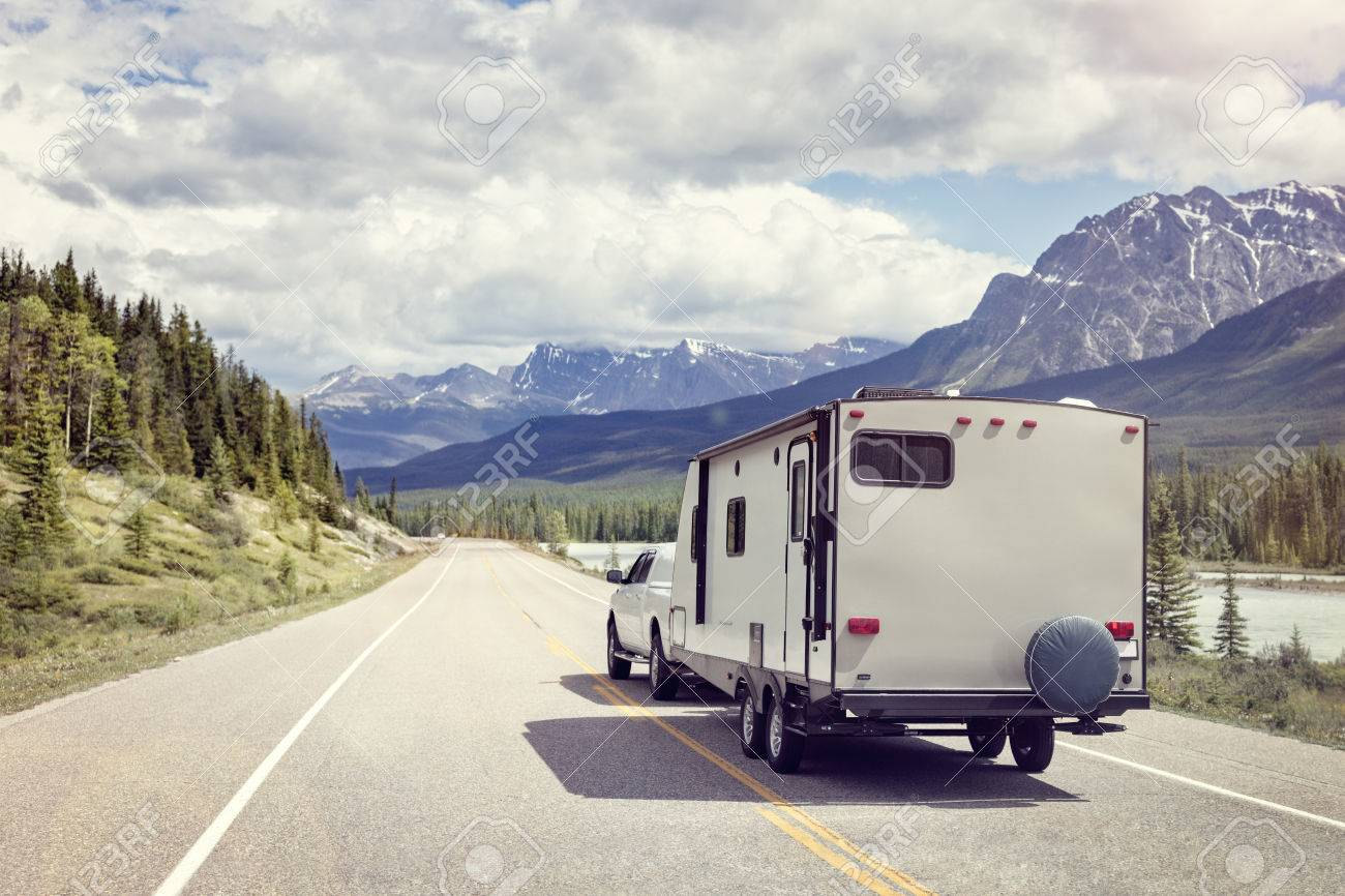 Caravan or recreational vehicle motor home trailer on a mountain road in Canada Standard-Bild - 66000336