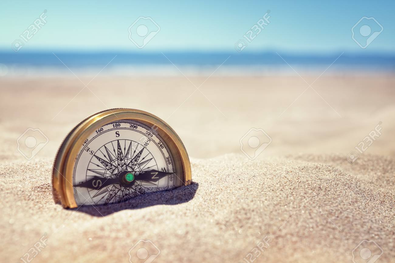 Golden compass buried in the sand on the beach concept for lost or direction - 87910711