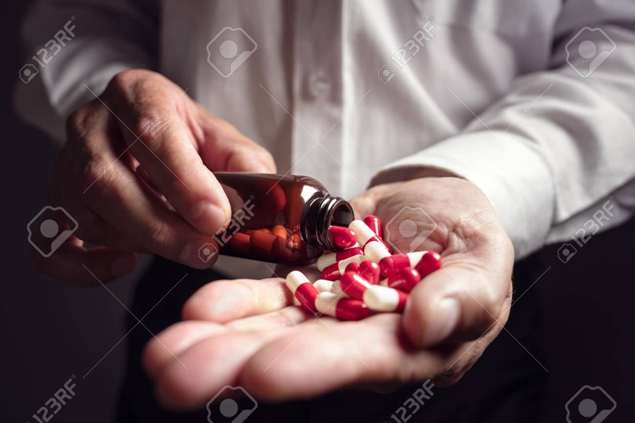 Pouring prescription drugs capsules from a pill bottle into hand - 87884676