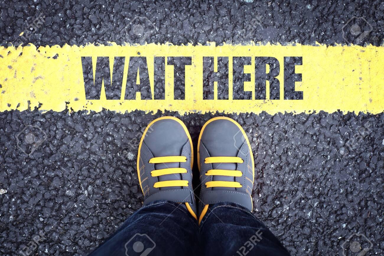 Wait here feet queue behind yellow waiting line - 131760252