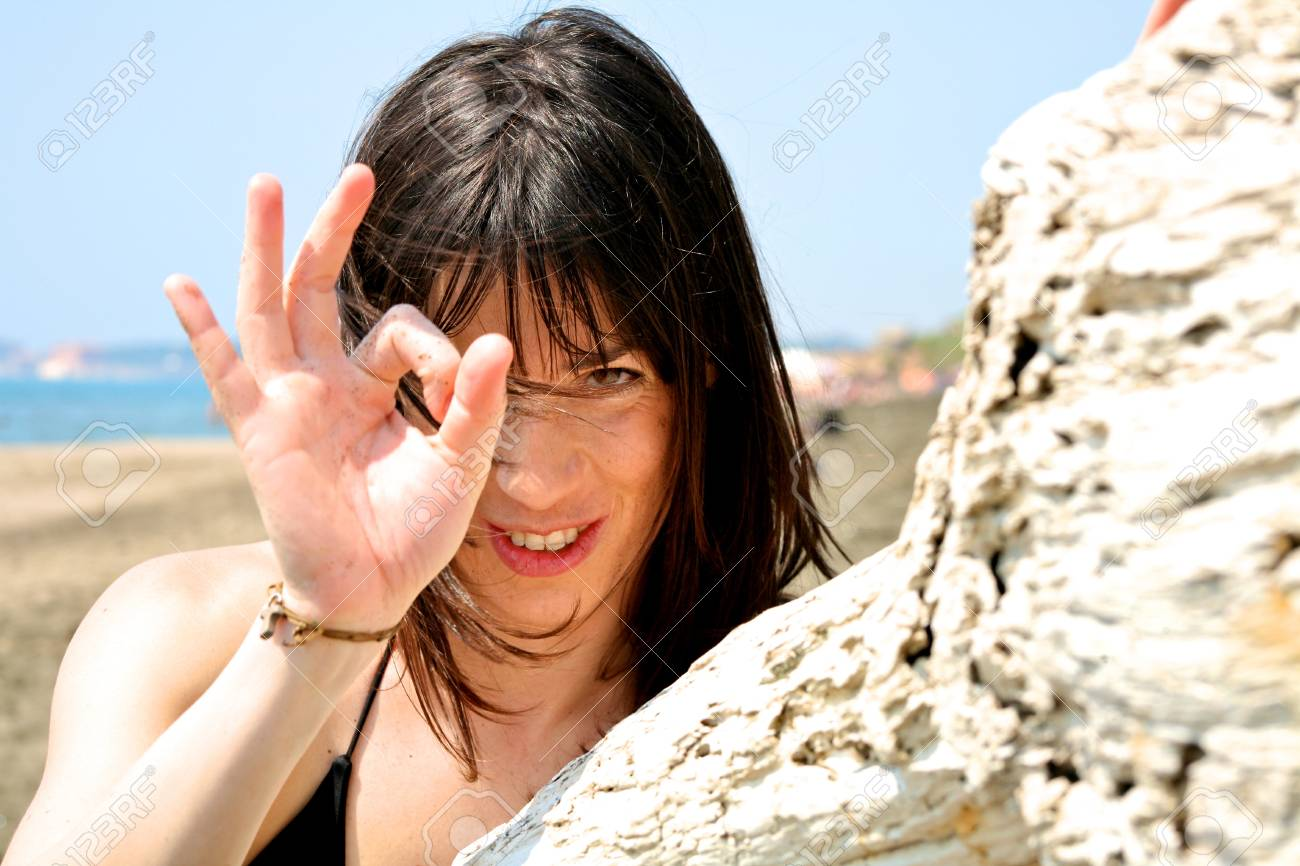 Happy female model on the beach with wind blowing in her hair smiling Stock Photo - 13133663