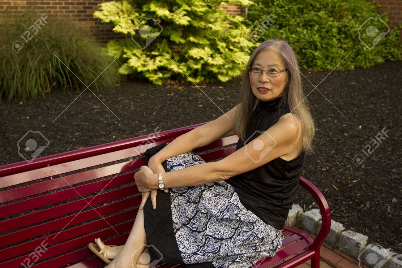 mature, senior asian woman seated on a red metal bench has feet