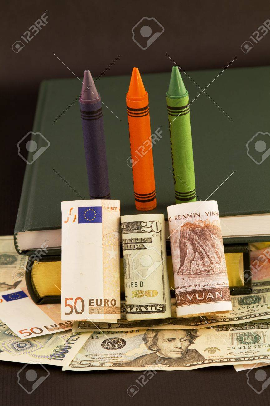Global emphasis on education symbolized in crayons, books, and multiple currencies, dollar, euro, and yuan Stock Photo - 8738658