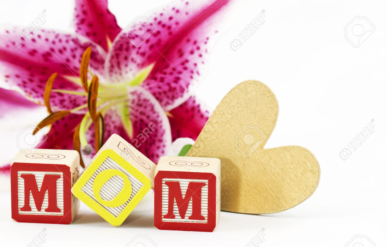 Gold Heart And Alphabet Block Letters Spelling MOM Are Placed In Front Of A Single