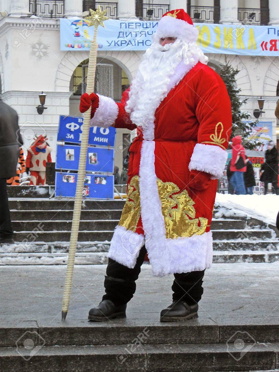 russian santa claus (Father Christmas) with magical wand in national red suite at the street before new year holiday in Kiev, Ukraine. Stock Photo - 11365736
