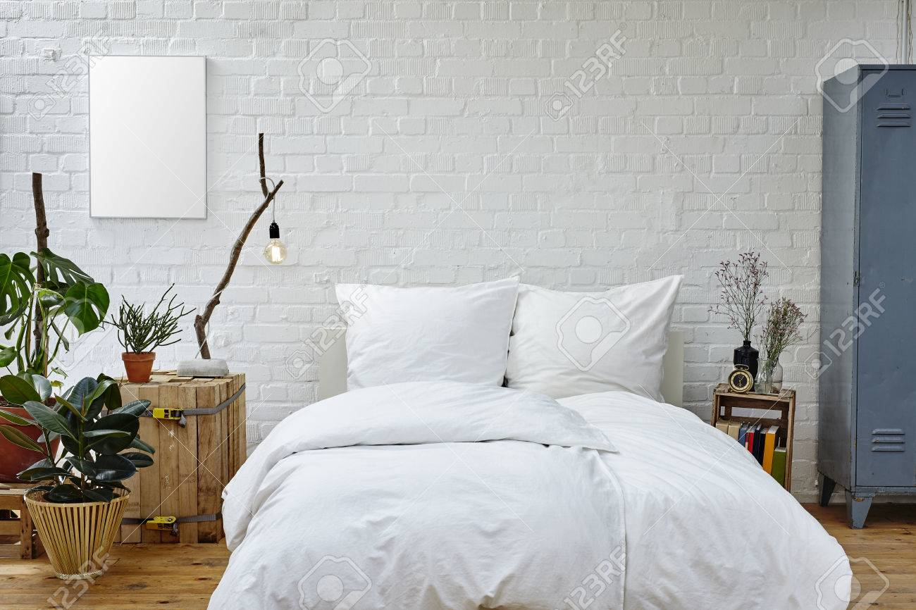 vintage urban bedroom white bedspread green plants and warm colors