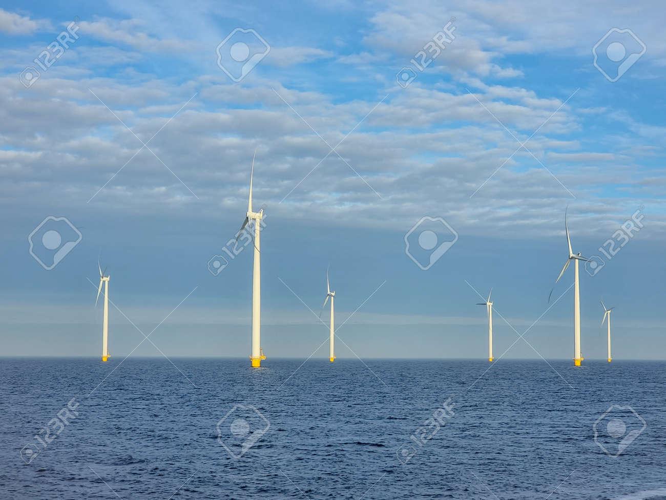 Windmill village indrustial wind mill by the lake Ijsselmeer Nehterlands. renewable energy green energy - 167511458