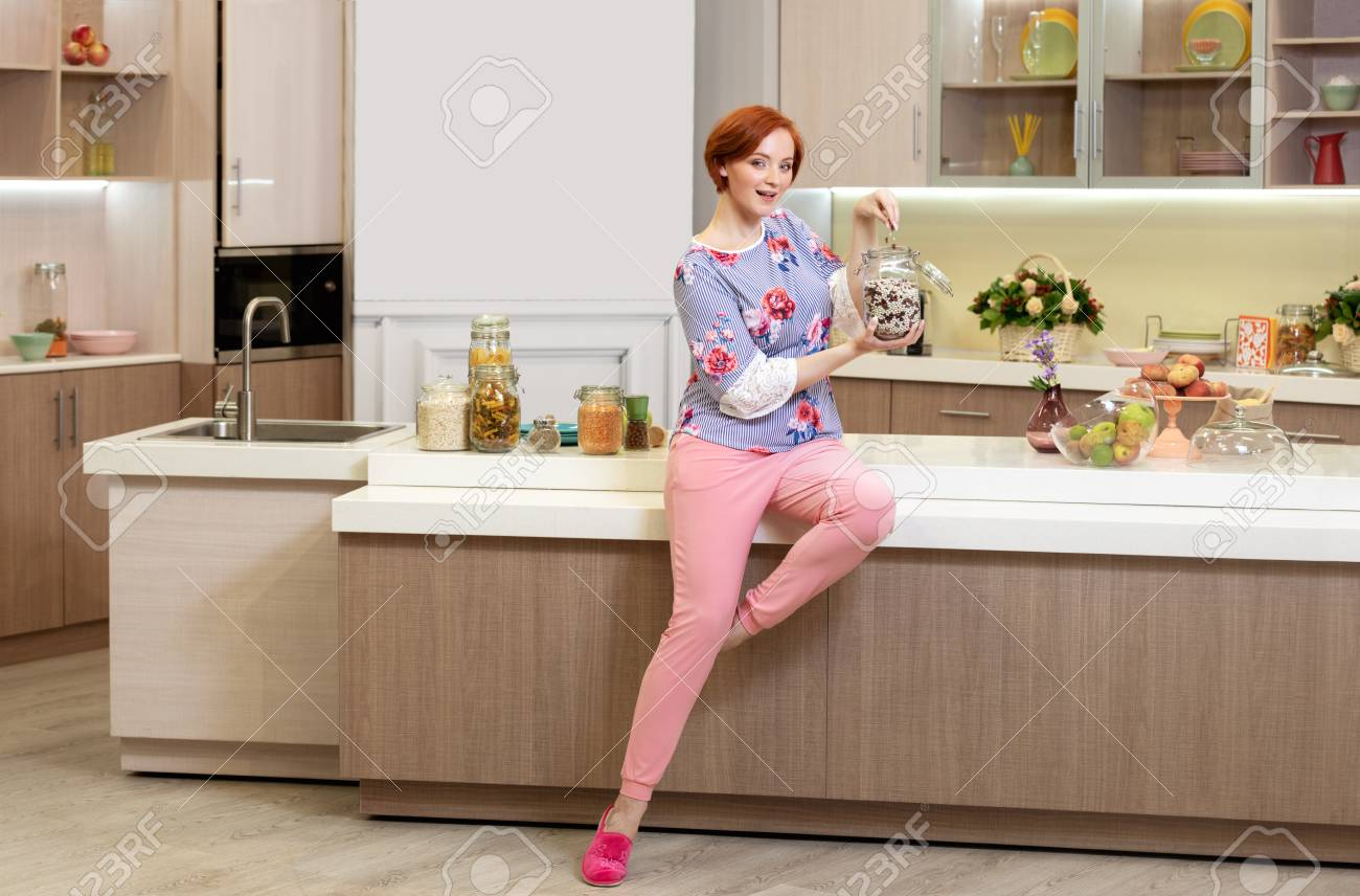 Girl With Red Hair In The Kitchen Among The Kitchen Set With Stock
