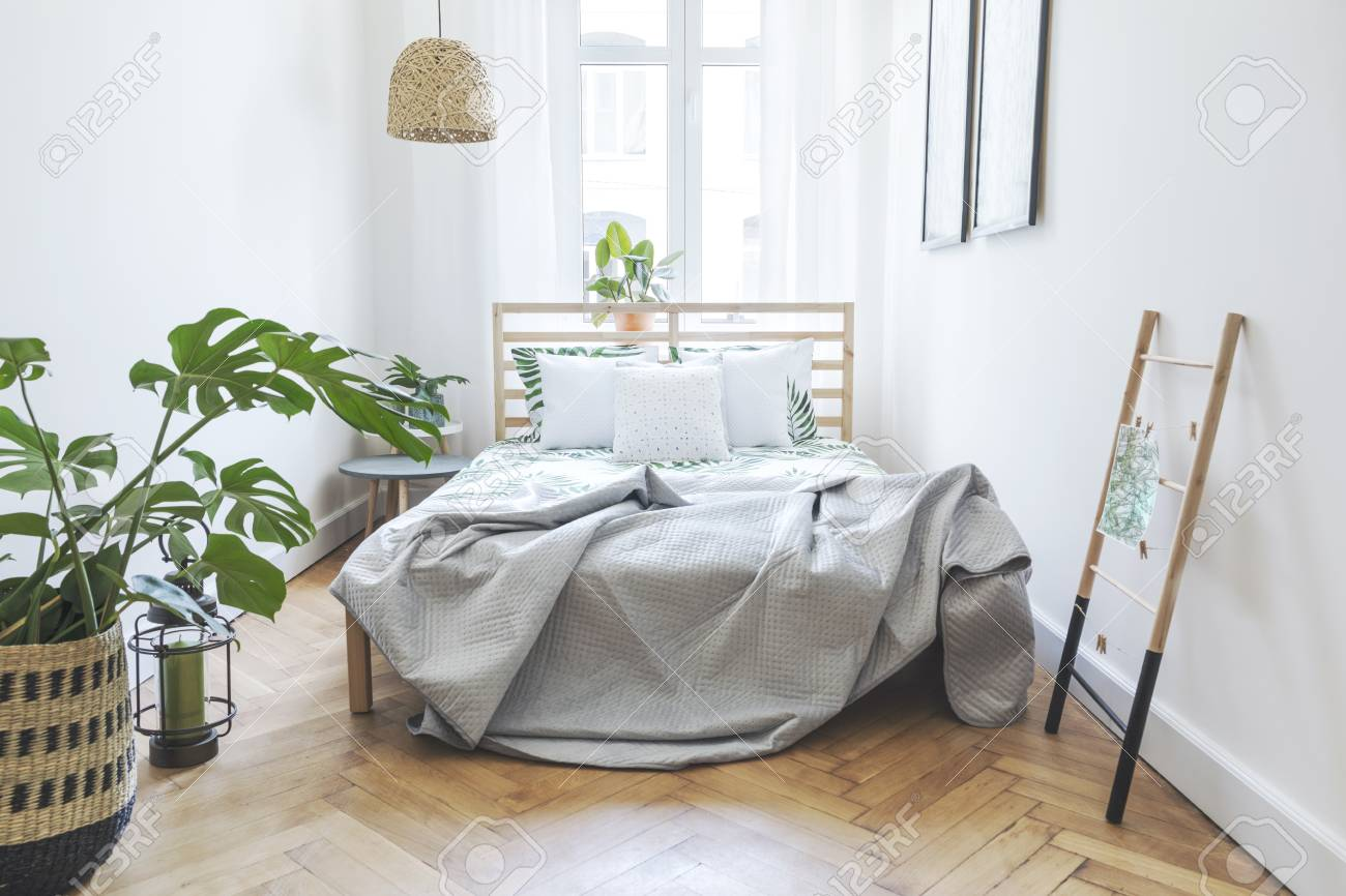 Modern scandinavian sunny bedroom with plants , floral pattern..