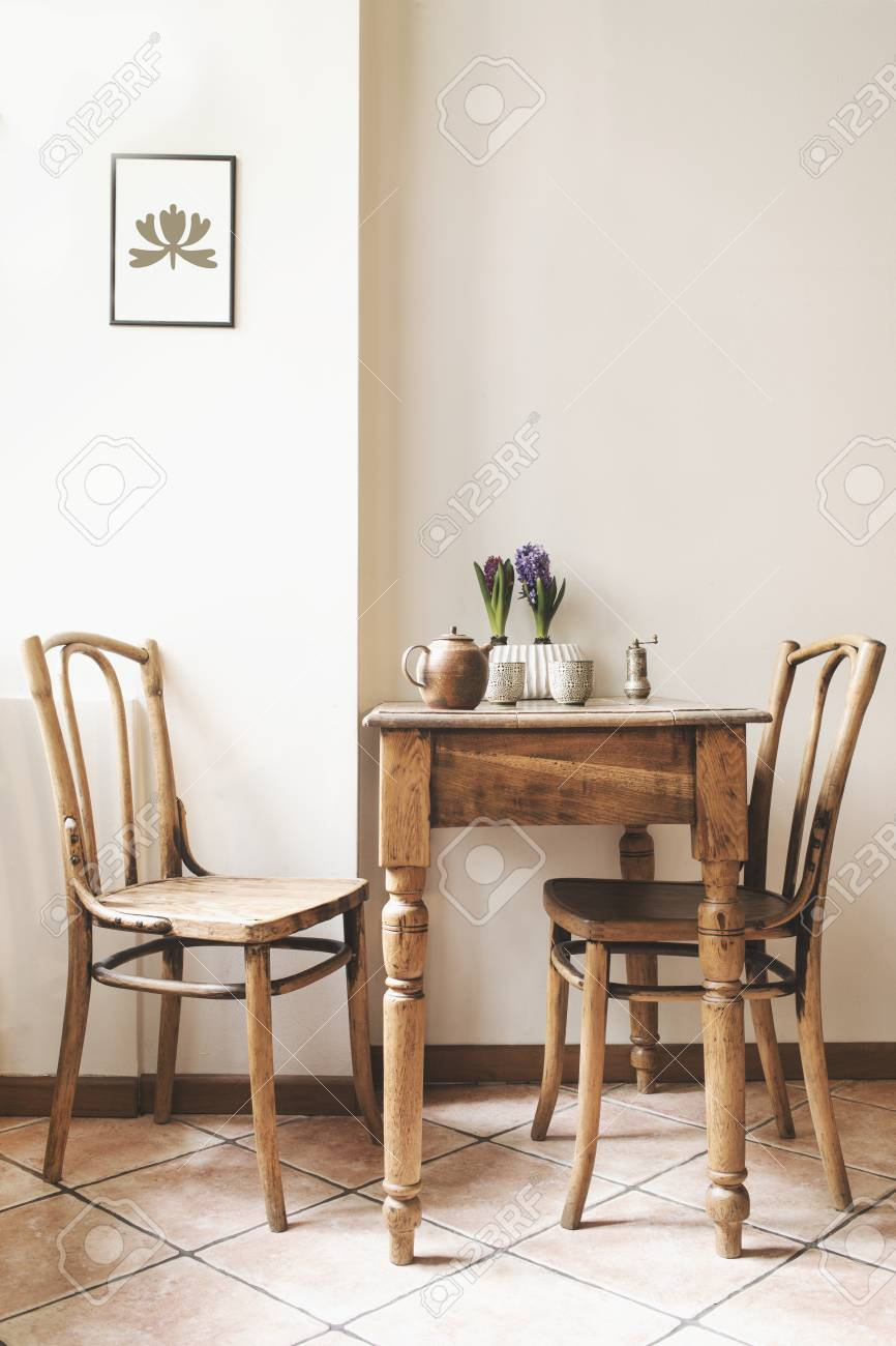 Vintage interior design of kitchen space with small table against white wall with simple chairs and plant decorations. Minimalistic concept of kitchen space. - 107550638