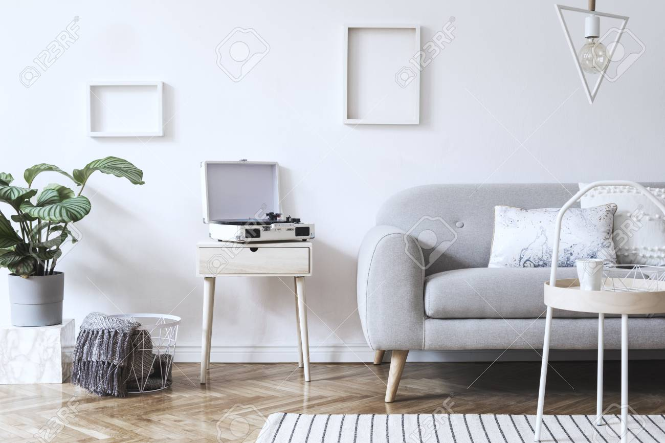 Stylish scandinavian white interior with design sofa, tropical plant, pillows, blanket, gramophone and mock up photo frames. White background walls, brown wooden parquet and modern triangle lamp. - 117682184