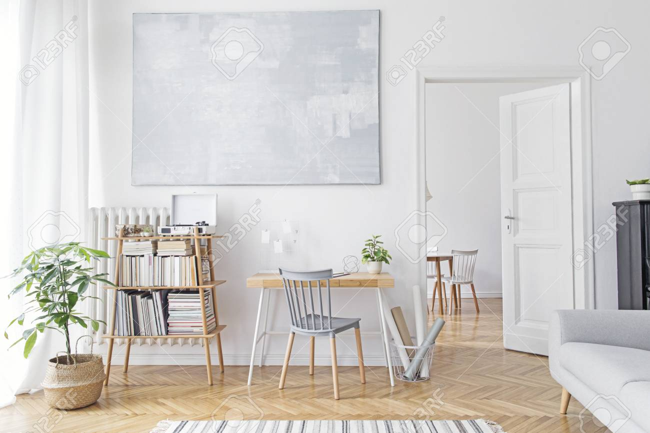 Stylish scandinavian home decor of interior with creative wooden desk, sofa, bamboo bookstand with accessories, books and plants Open space and living room. Brown wooden parquet and stylish carpet. - 120054940