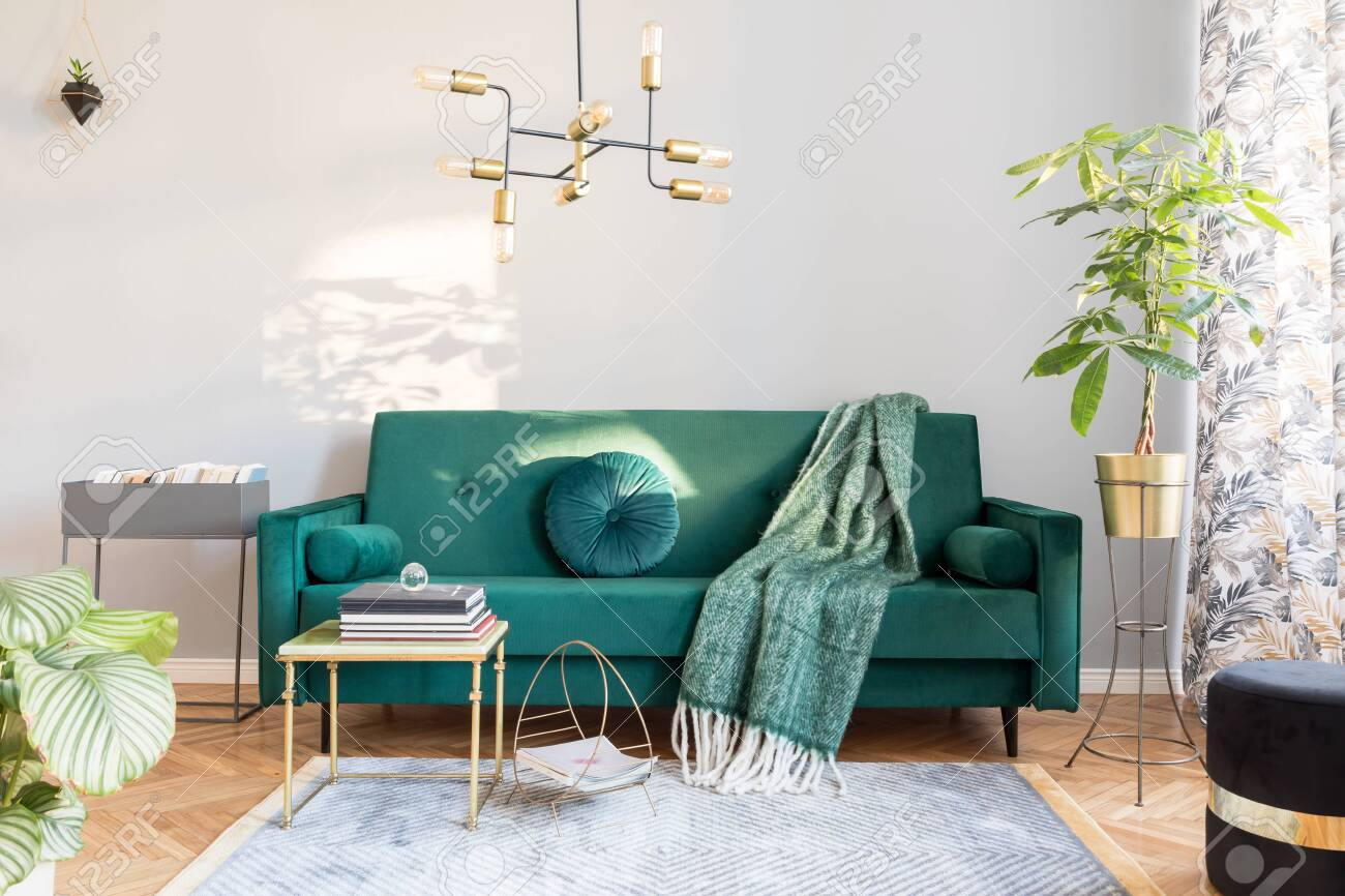 Stylish sunny decor of living room with design green velvet sofa,..
