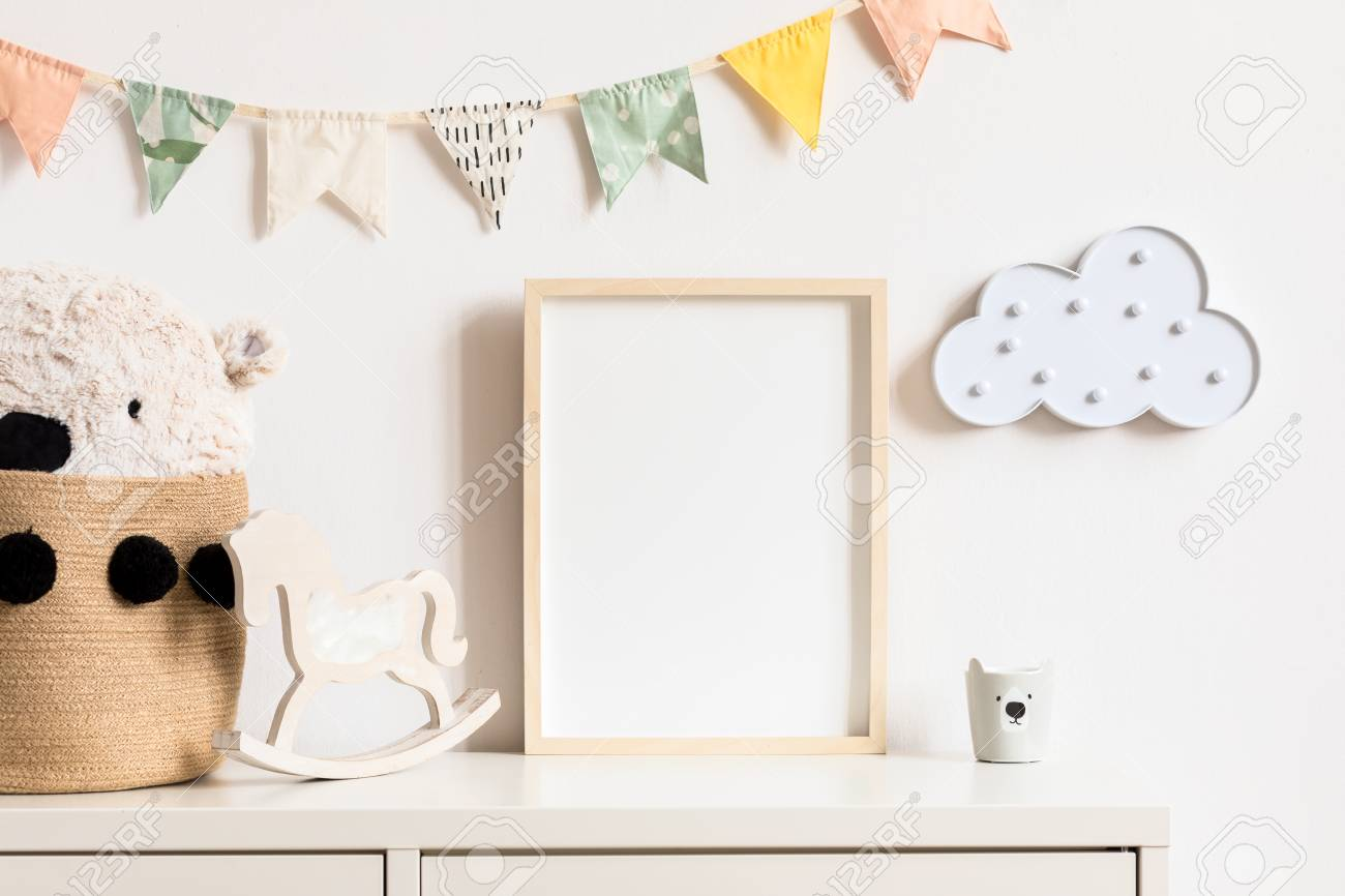 Stylish and modern scandinavian childroom interior with mock up photo or poster frame on the white shelf. Toys, teddy bear in basket, rocking horse and hanging cotton colorful flags and cloud. - 122001431