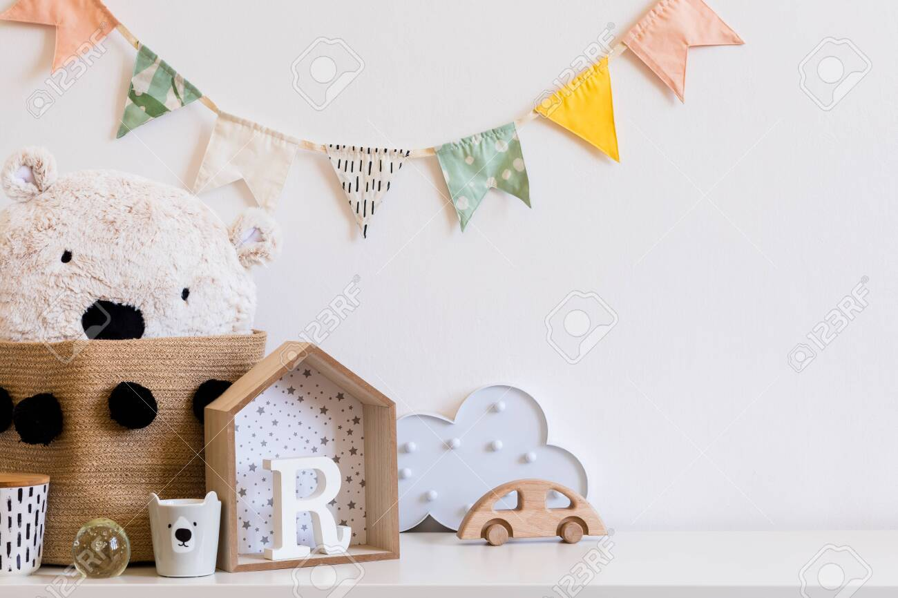 Stylish scandinavian child room with hanging cotton colorful flags on the white wall, boxes, teddy bear in natural basket, toys. wooden accessories and cloud. Real photo. Copy space for inscription. - 122253350