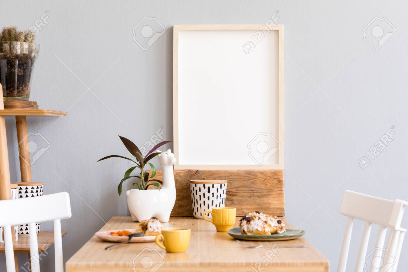 Stylish and sunny interior of kitchen space with small wooden table with mock up photo frame, design cups and tasty dessert. Scandinavian room decor with kitchen accessories, cacti and plants. - 122253353