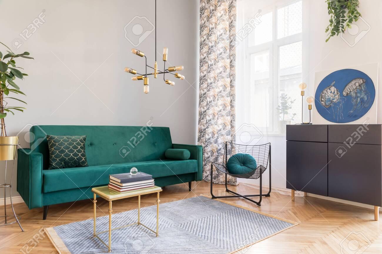 Stylish decor of living room with design green velvet sofa, plants,..