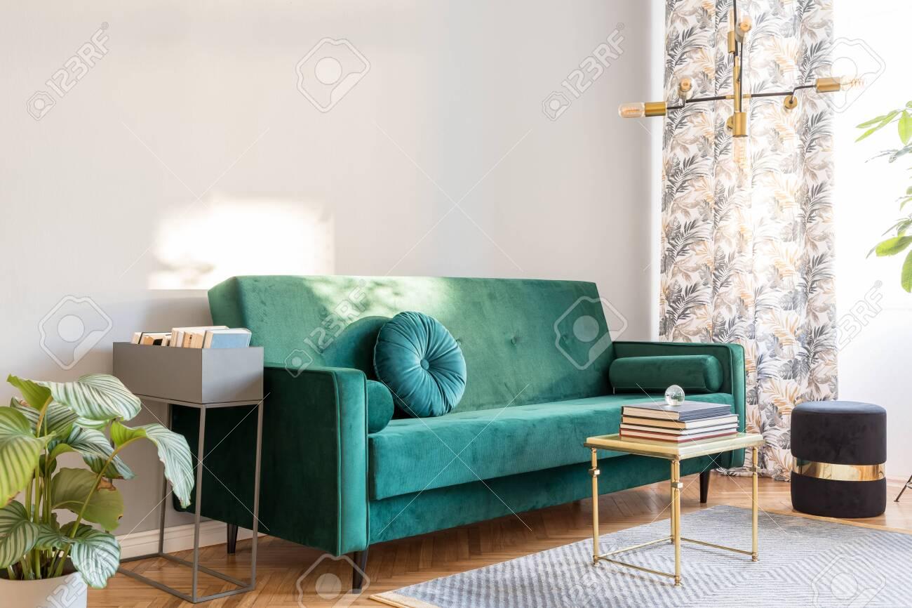 Stylish sunny decor of living room with design green velvet sofa,..