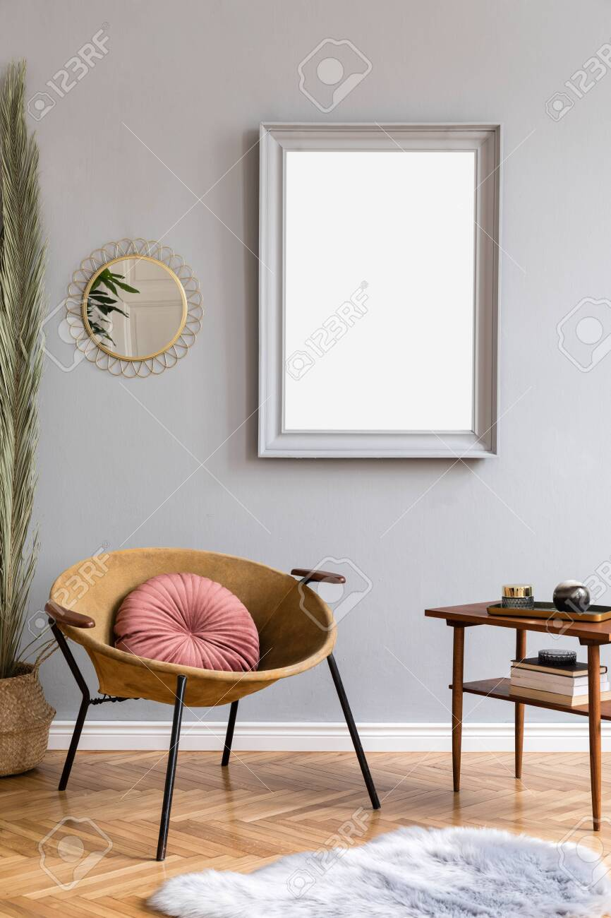 Stylish and luxury interior of with design honey yellow armchair, gray mock up frame, gold mirror, palm leaves and pillow Retro small table with elegant accessories. Modern home decor of living room. - 123191345