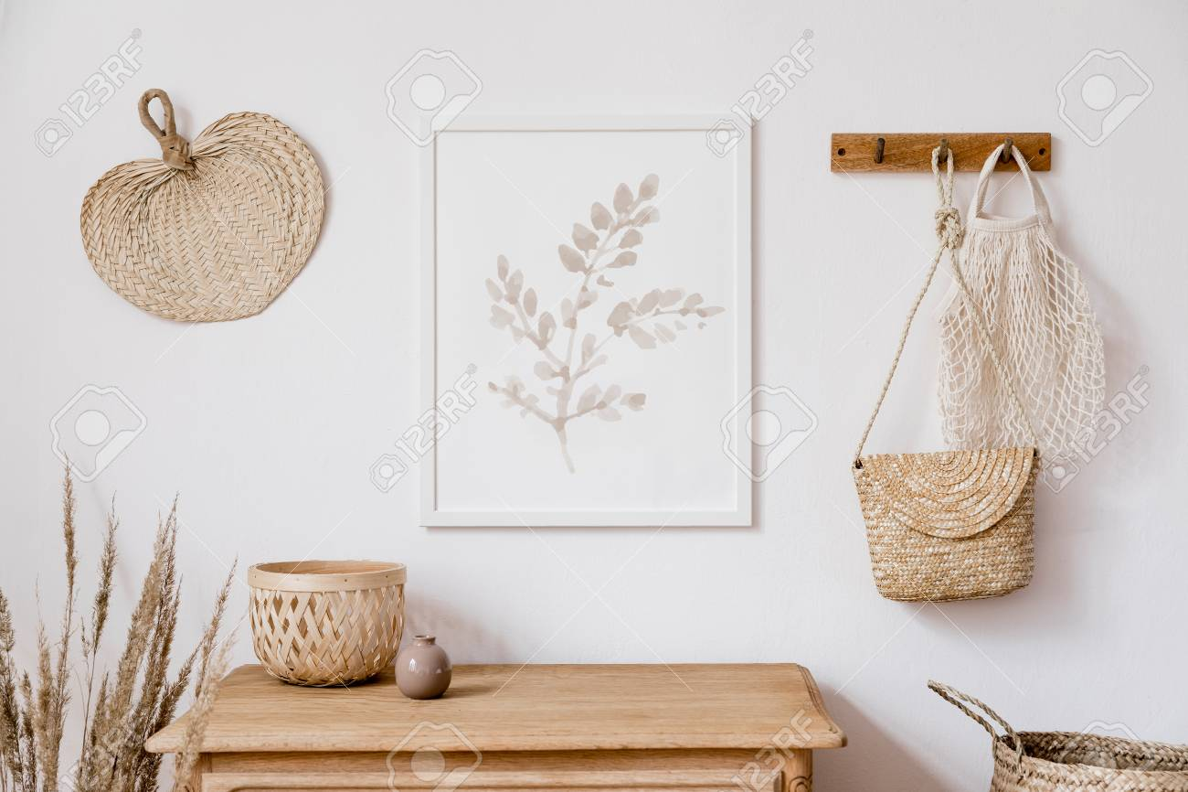 Stylish korean interior of living room with brown mock up poster frame, elegant accessories, flowers in vase, wooden shelf and hanging rattan leaf, bags. Minimalistic concept of home decor. Template. - 125590528