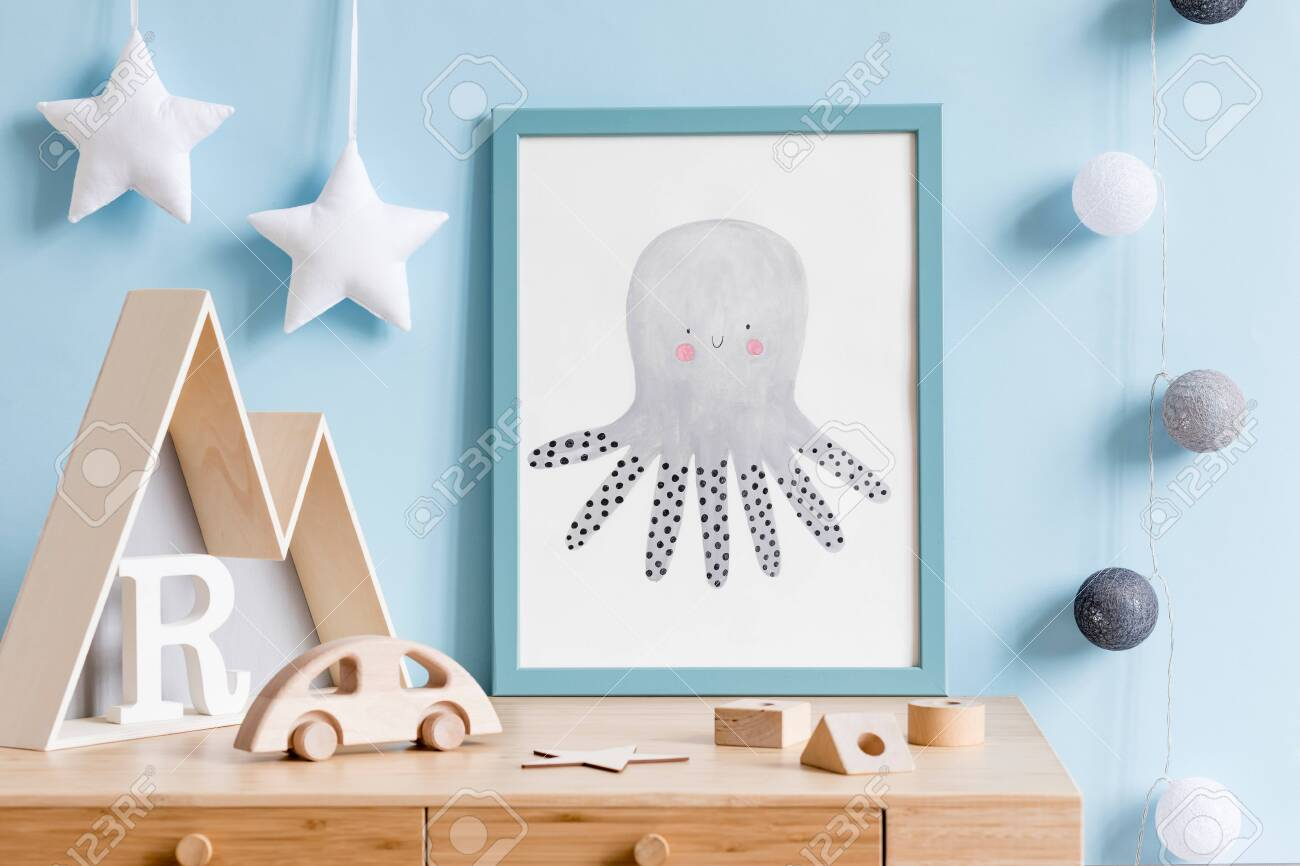 The modern scandinavian newborn baby room with mock up poster frame, wooden toys, mountain box and children accessories. Minimalistic and cozy interior with blue walls. Haniging cotton balls and stars - 126516054