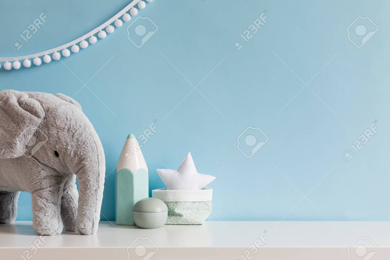 Cozy scandinavian newborn baby room with gray plush elephant ,white stars lamp and children accessories. Stylish interior with blue walls and haniging white garland. Template. Copy space. - 126277365